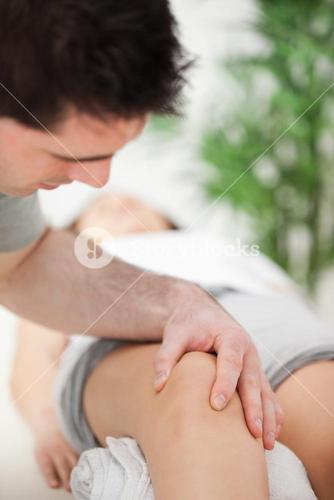 Serious doctor looking at the knee of a patient