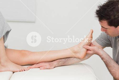 Physiotherapist looking at the foot of a patient