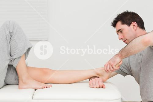 Serious doctor stretching the foot of his patient