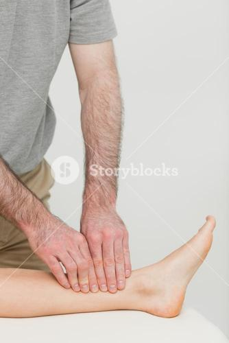 Fingertips massaging a shin bone
