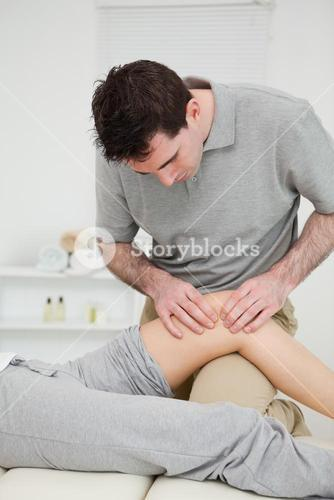 Physiotherapist pressing on the knee of a patient