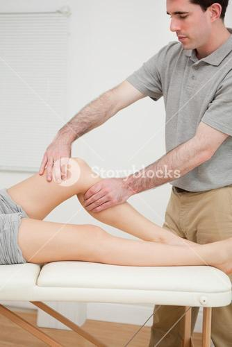 Serious brunette doctor holding the knee of his patient