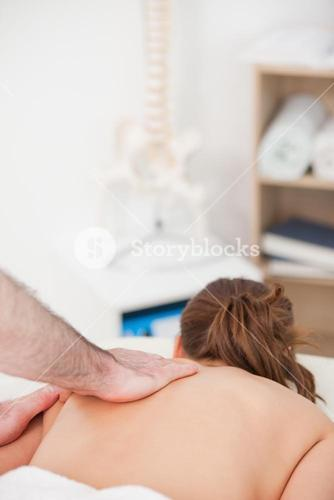 Woman being massaged while lying on the belly