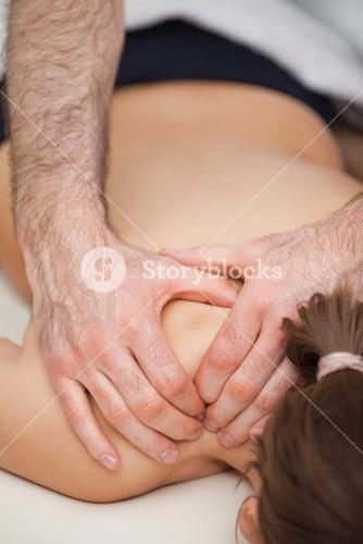 Osteopath pressing the shoulders of his patient while using his two hands
