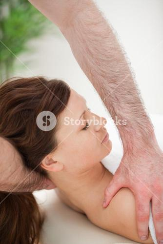 Therapist manipulating the neck of his patient while holding her shoulder