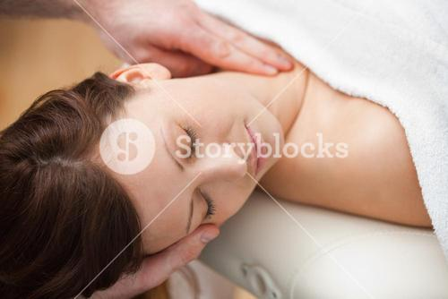 Doctor holding the head of a woman while massaging her neck