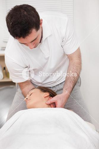 Therapist manipulating the neck of his patient while standing