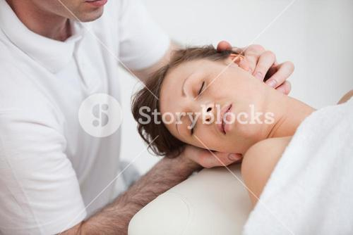 Woman being massaging by the doctor while having the head turn in the side