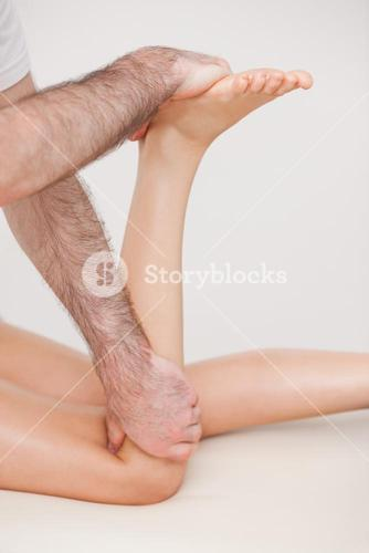 Podiatrist manipulating the leg of his patient while holding his foot and his knee