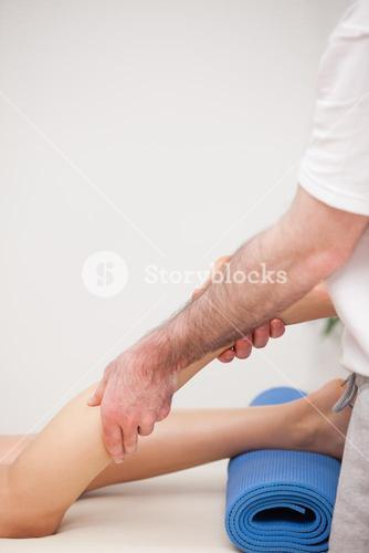 Podiatrist massaging the leg of his patient while standing