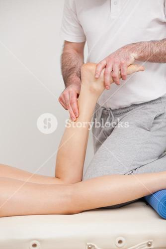 Podiatrist massaging the ankle of a woman