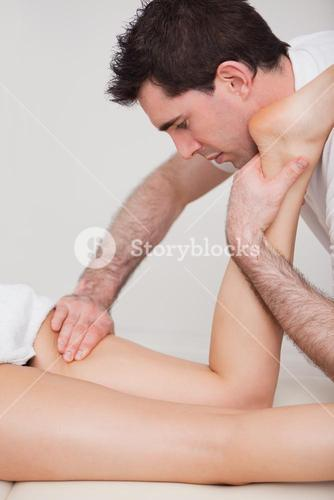 Chiropractor manipulating the leg of his patient while folding it