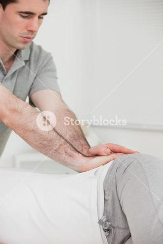Serious chiropractor pressing the hip of his patient