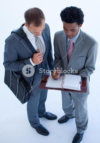 Businessmen writing in a business diary