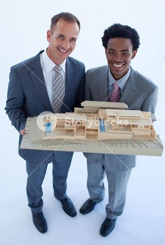 Architects holding a model house