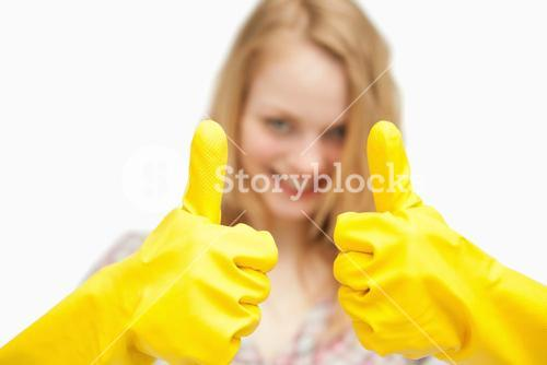 Woman thumbs up while wearing cleaning gloves