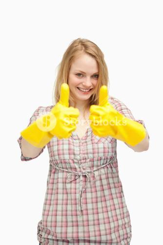 Young woman wearing cleaning gloves while thumbs up