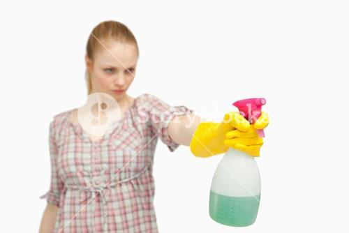 Serious woman holding a spray bottle