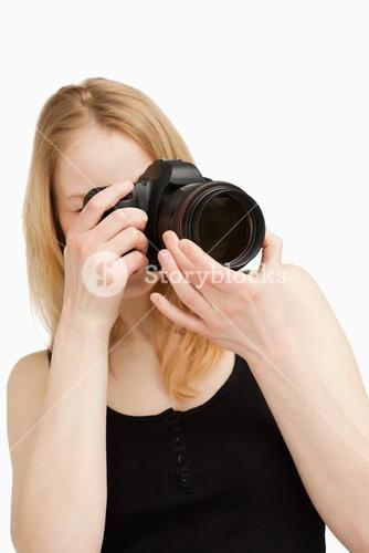 Young woman aiming with a camera
