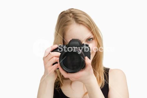 Fairhaired woman aiming with a camera