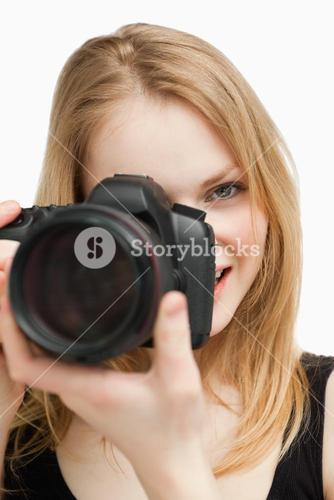 Blonde woman aiming with a camera
