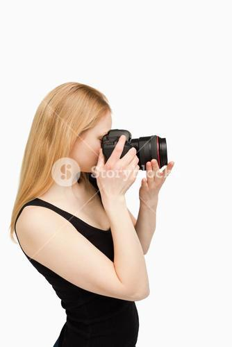 Blondehaired woman aiming with a camera