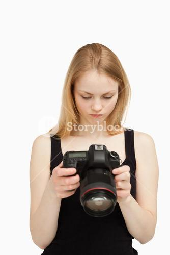 Woman looking at the screen of her camera