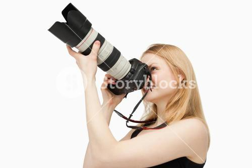 Woman aiming with a SLR camera while smiling