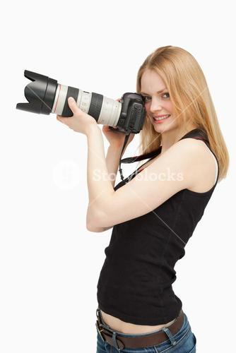 Joyful woman holding a SLR camera