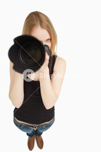Blondehaired girl aiming with her SLR camera