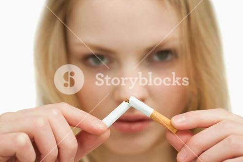 Close up of a young woman breaking a cigarette