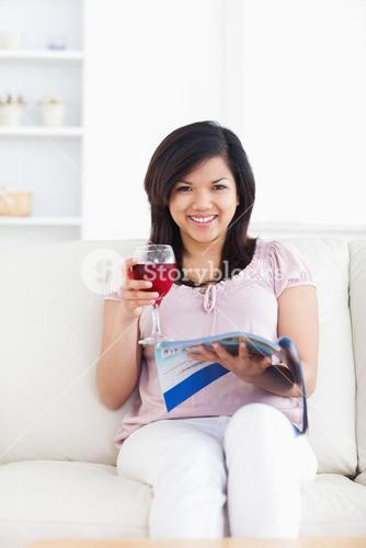 Woman looking ahead as she reads a magazine and holds a glass of red wine