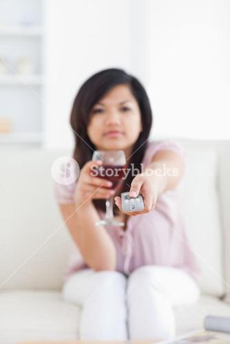 Blurred woman holding a glass of red wine and a television remote