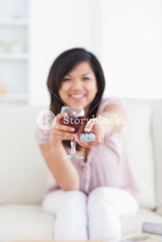Woman drinking a glass of wine while holding a television remote