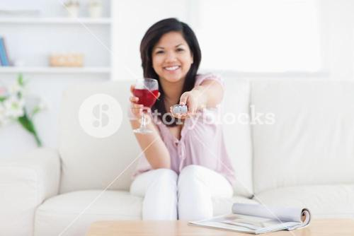Woman sitting in a white couch while holding a glass of red wine and a television remote