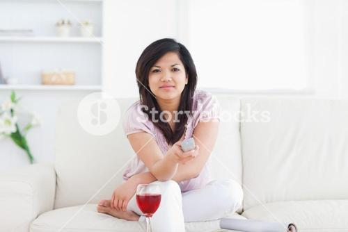Woman sitting on a couch while holding a remote