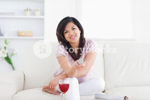 Woman sitting on a couch and holding a television remote