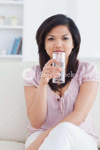 Woman sitting on a couch and holding a glass of water