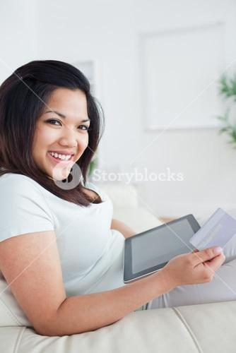 Woman smiling while holding a card and a tactile tablet