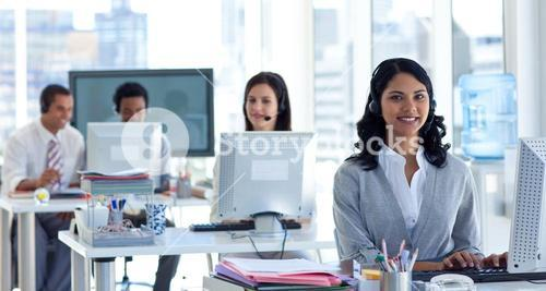 Businesswoman with a headset on in a call center