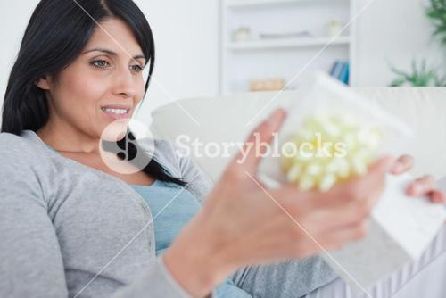 Woman sitting on a couch while opening a gift box