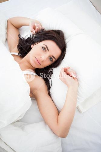 Brownhaired woman lying while stretching her arms
