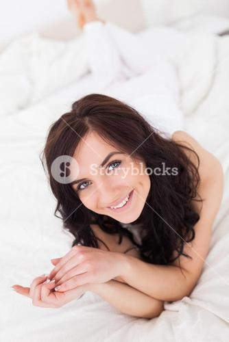 Happy brownhaired woman lying on her blanket