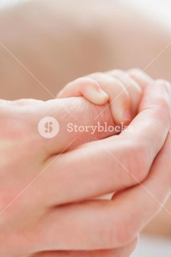 Hand holding the little hand of a baby