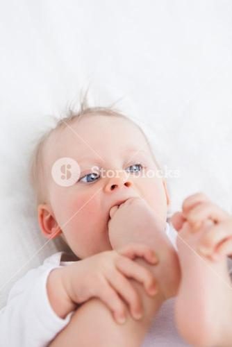 Cute baby placing her foot on her mouth