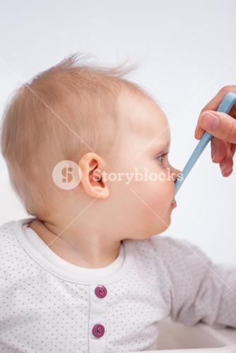 Cute baby eating with a spoon