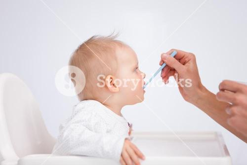 Baby eating her meal with a spoon