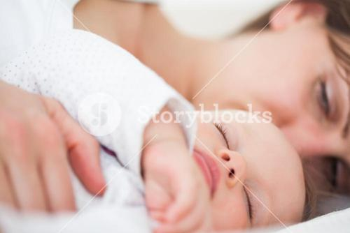 Woman and her baby lying side by side