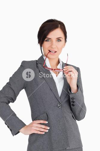 Seductive business woman putting her glasses in her mouth