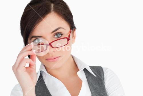 Blue eyed businesswoman holding her glasses